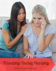 Friend comforting her crying friend at home on the couch