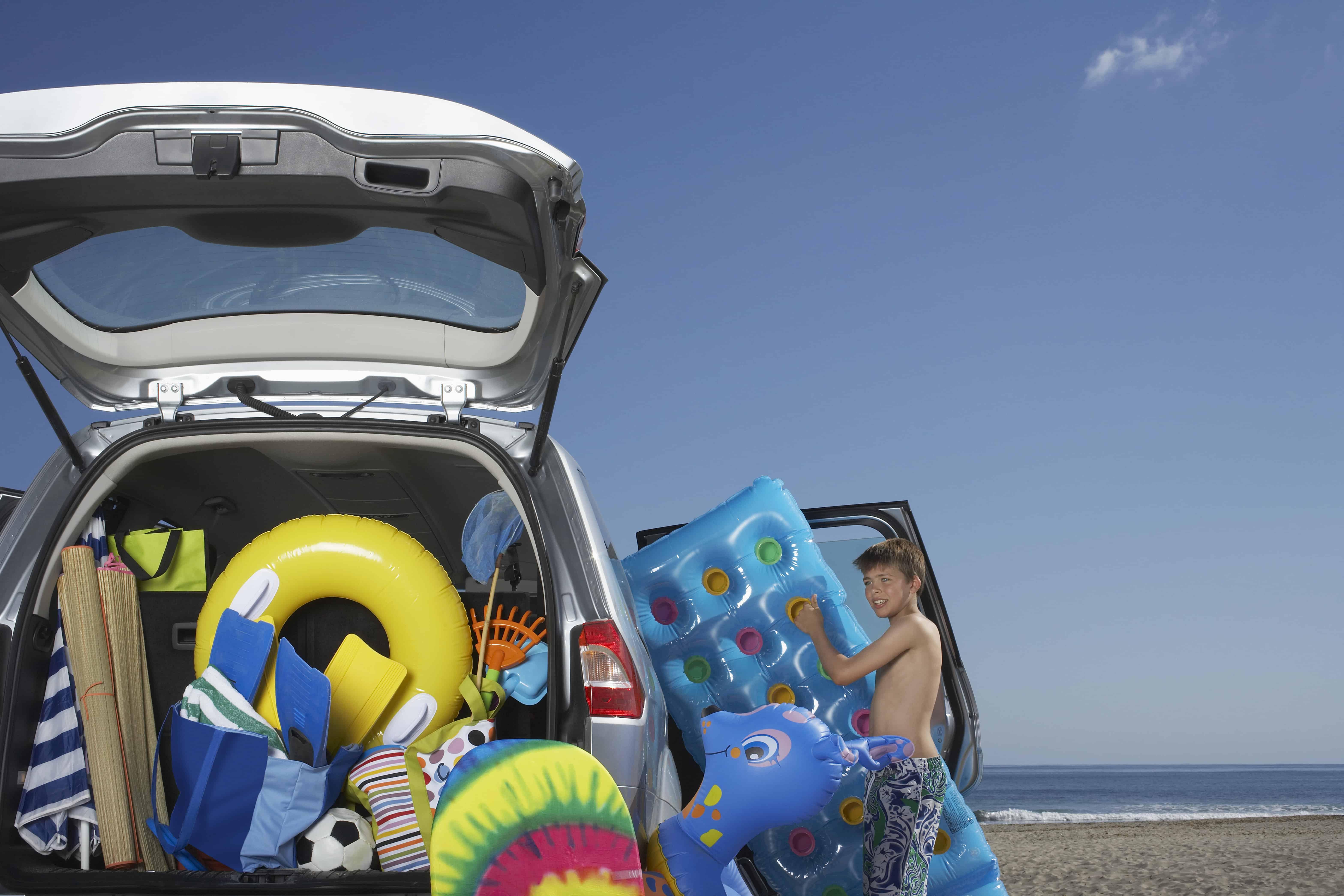 Boy (10-12) unloading air mattress from car full of beach accessories for summer organization