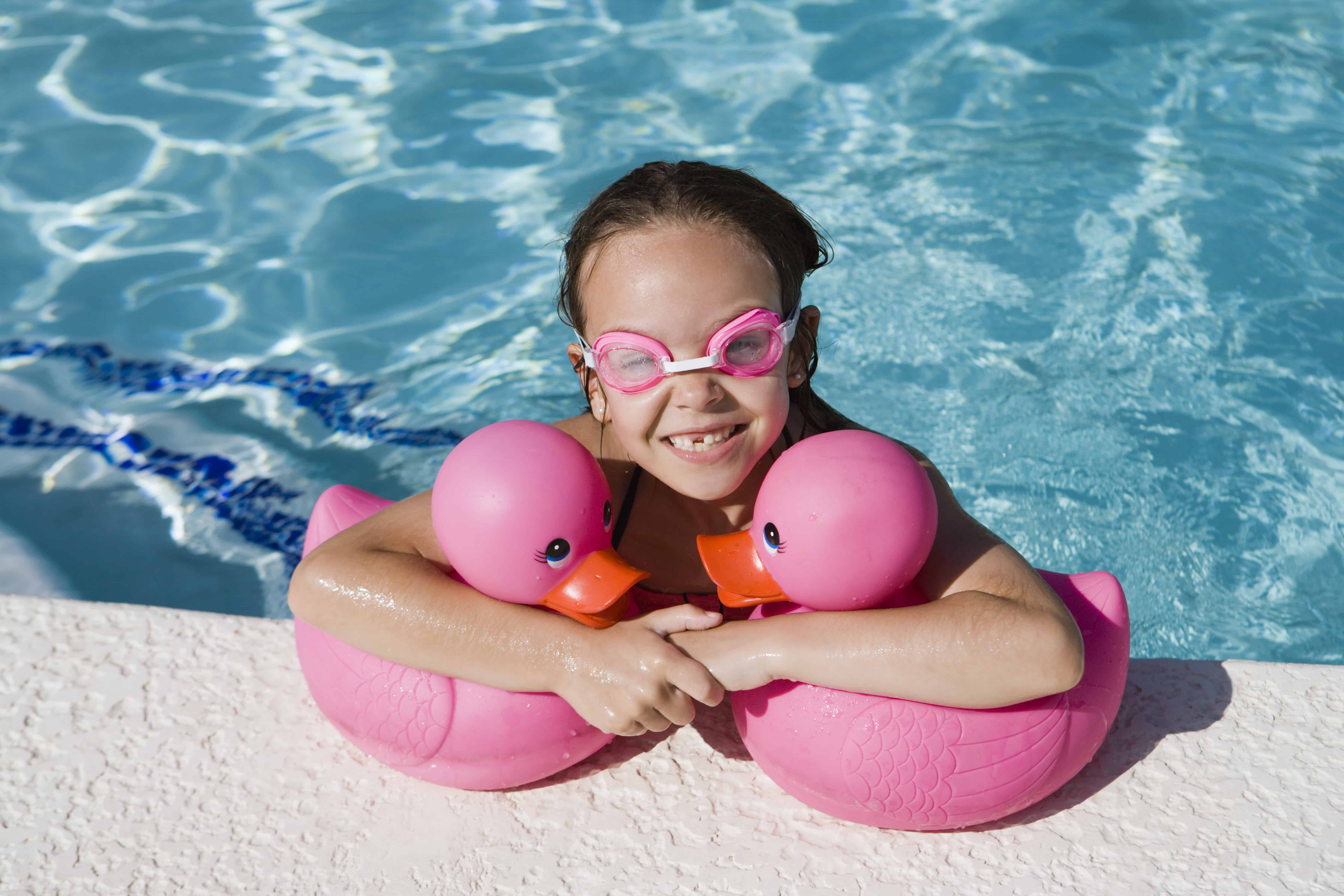 Girl at Pool Side Holding Pink Rubber Ducks for summer organization tips