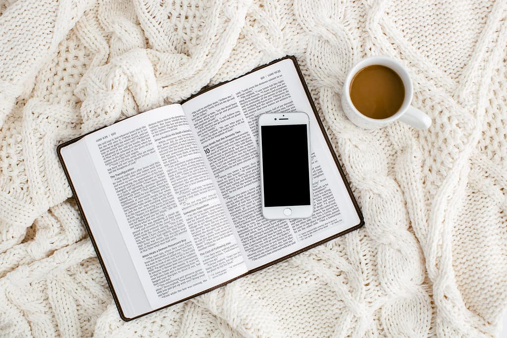 Bible, phone, and coffee cup on a blanket showing God's Word is the cornerstone for an abundant life