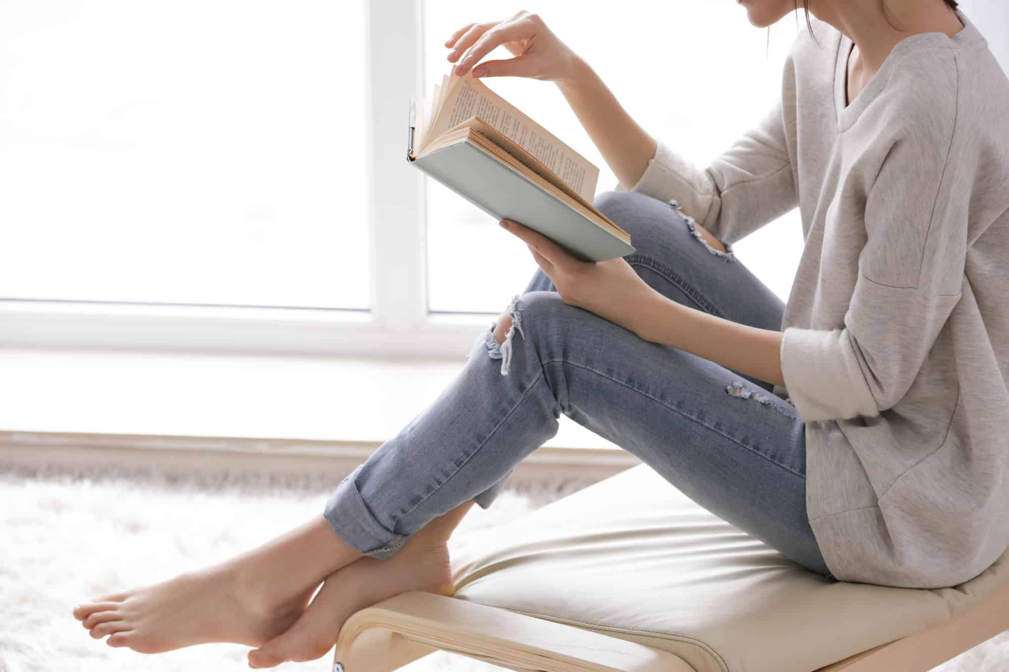 Beautiful young woman reading near window at home and meditating on God's Word