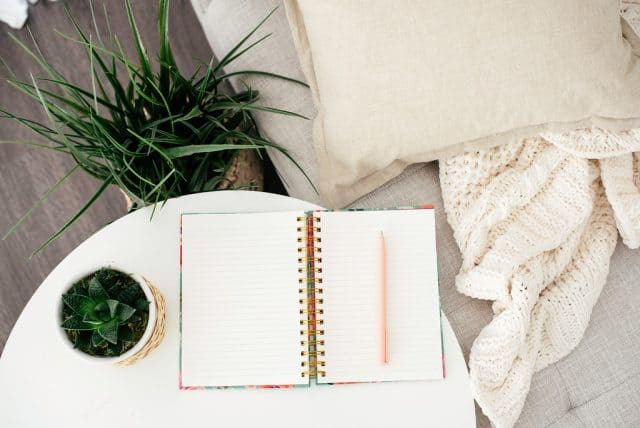 open prayer journal on table with blanket and couch next to it