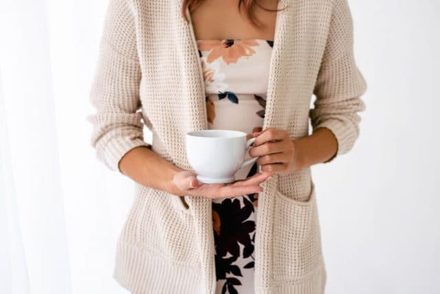 woman holding a coffee cup and thankful for an abundant life in Christ
