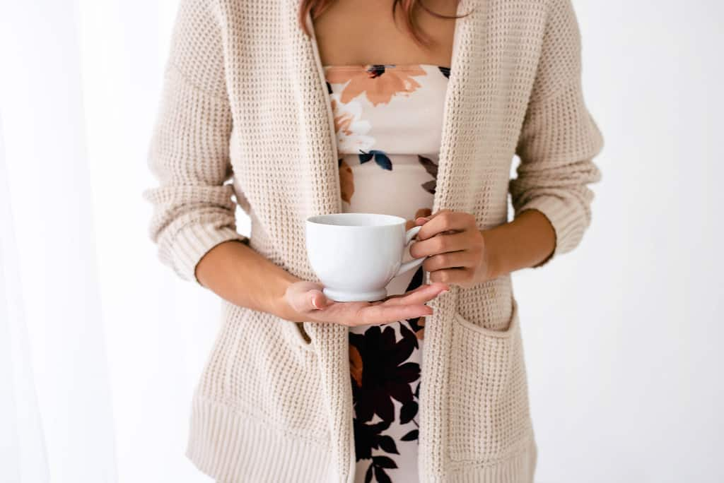 woman holding coffee cup in palm of her hand