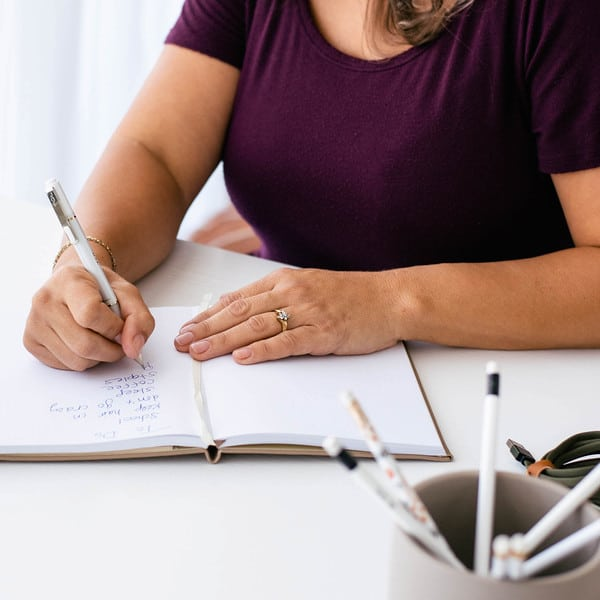 woman writing at desk with black shirt and white notebook