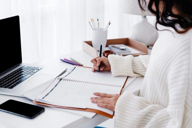 woman at white desk writing in a planner with a white shirt
