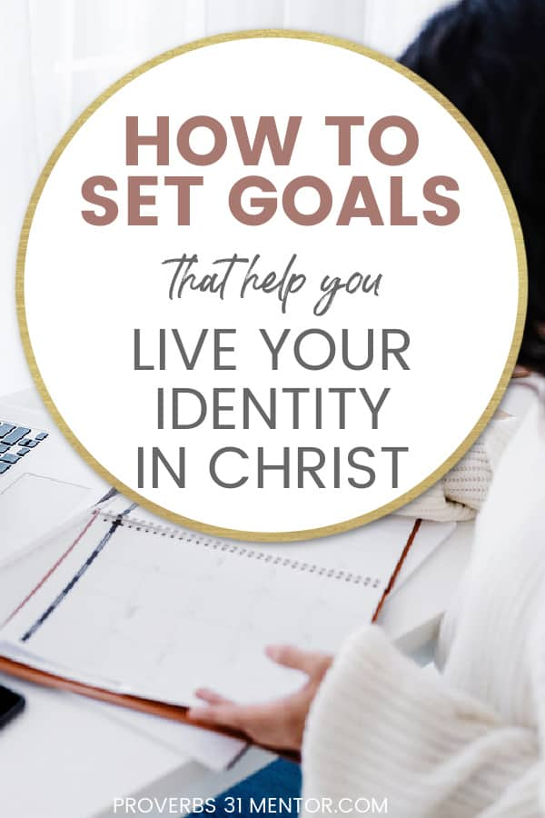 title- how to set goals that help you live your identity in Christ picture- woman in white shirt at white desk writing in a planner