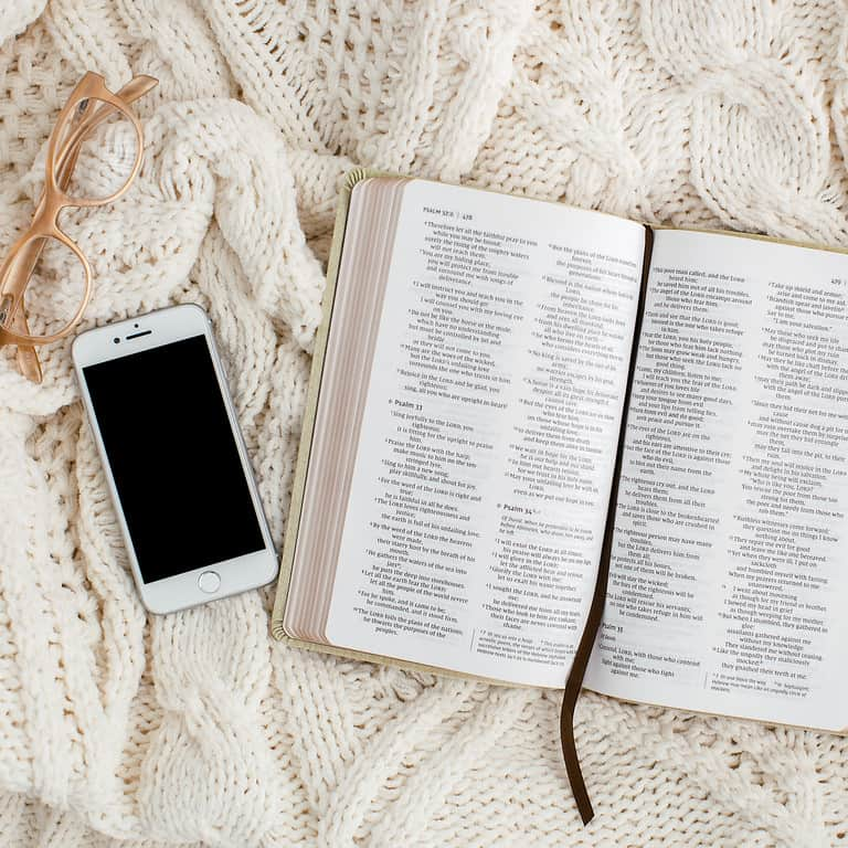 open Bible and phone on a blanket