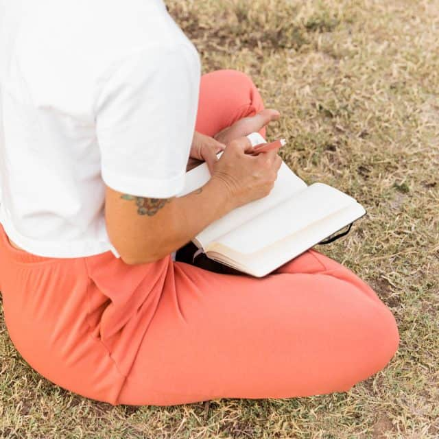 girl writing in journal in pink pants